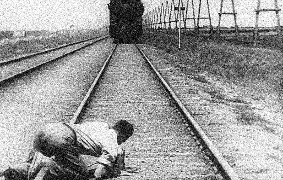 지가 베르토프(Dziga Vertov)가 (1929)에서 무릎을 꿇고 기차를 촬영하고 있다.